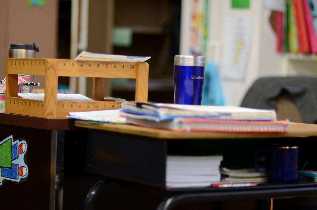 Teacher's desk with an Ursuline travel coffee mug on top