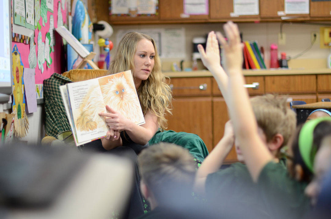 Teacher reading a book to young students