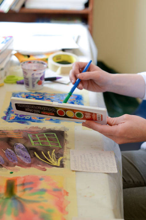 Student paints with watercolor at Ursuline's art therapy school