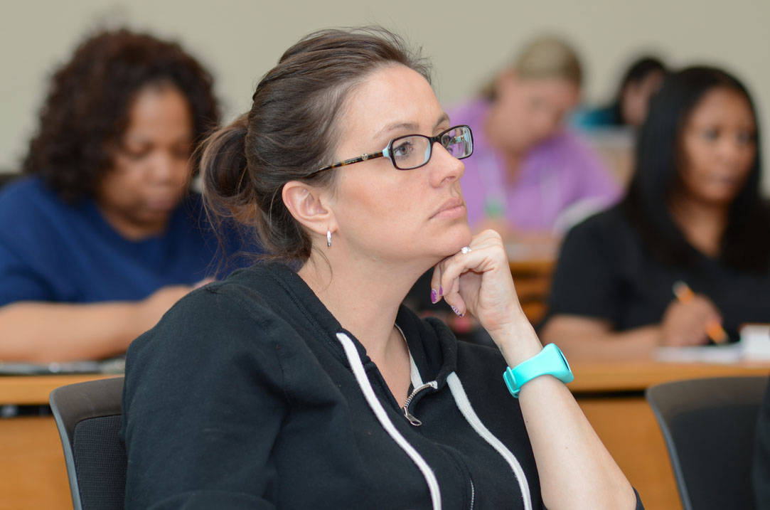 Nursing student listens to professor in class