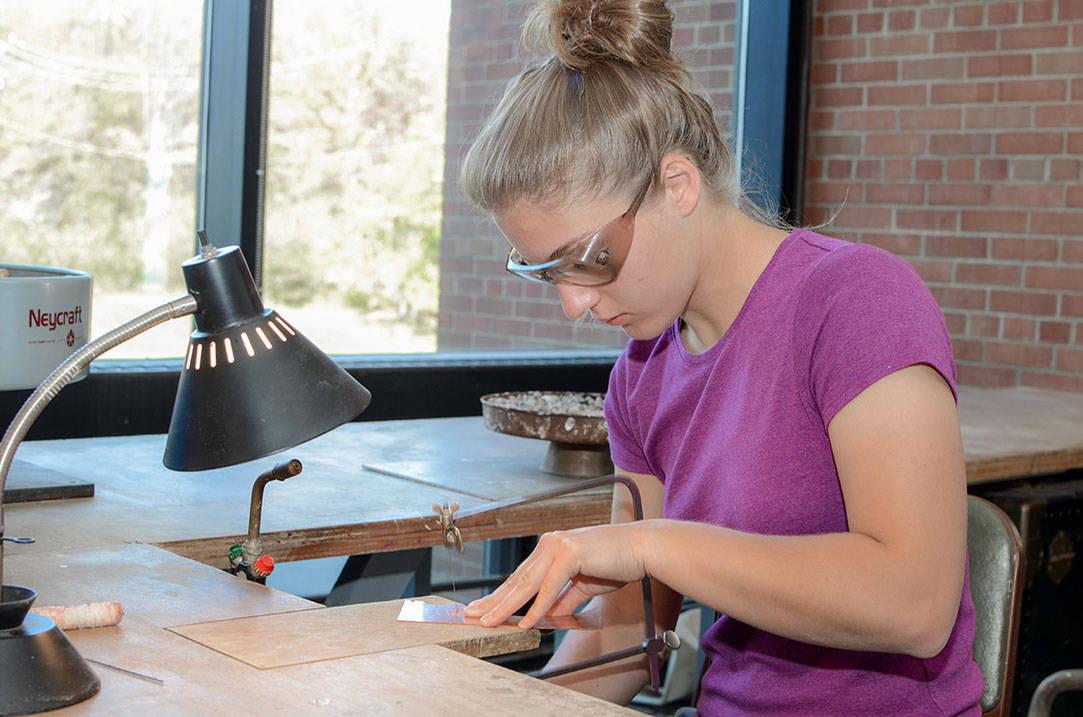 Student saws design on copper