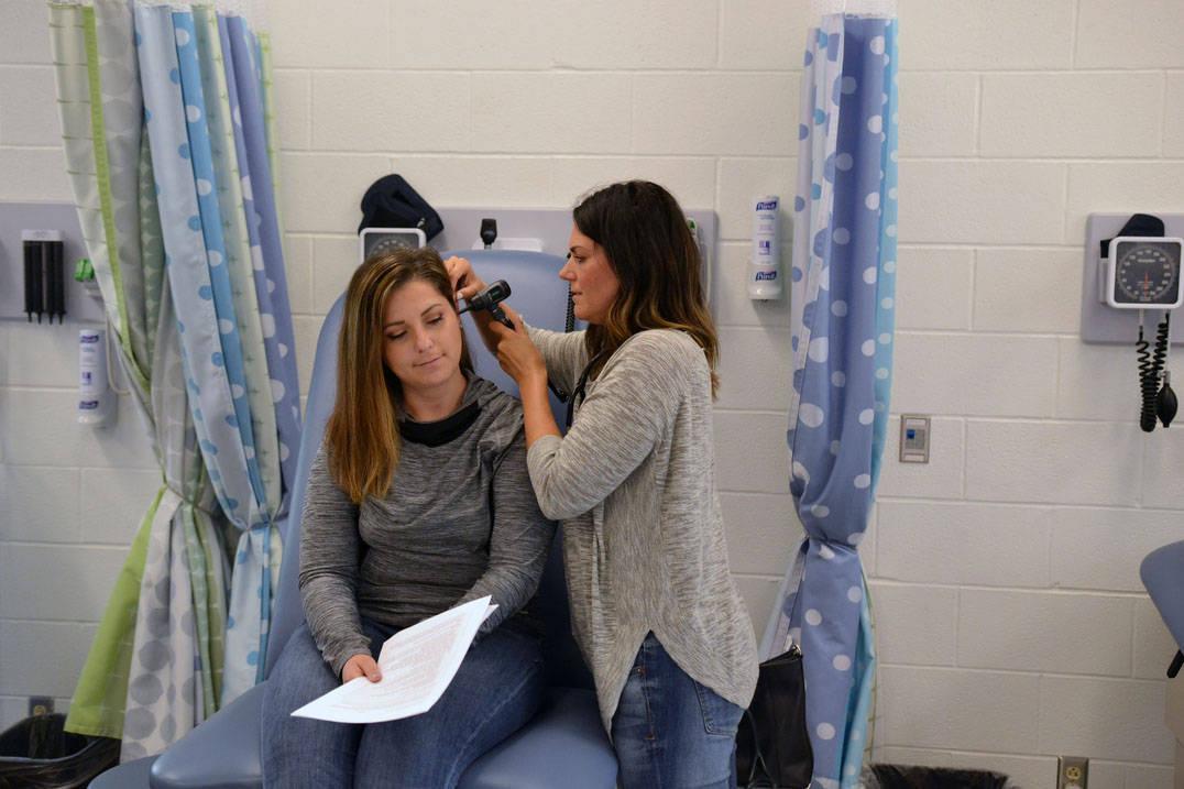 Student examines classmate's ear in nursing lab