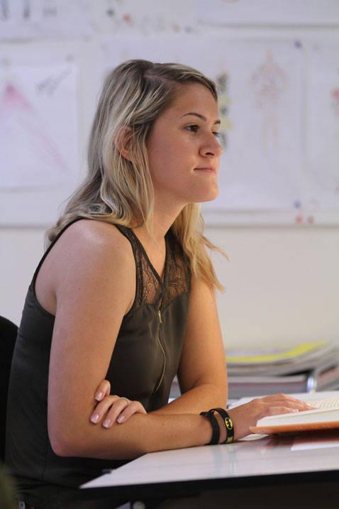 Fashion merchandising degree student listening to professor in class