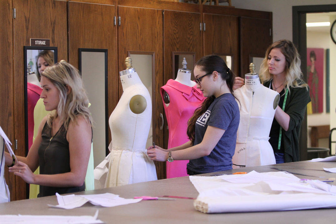 Fashion design degree student measuring form and draping fabric