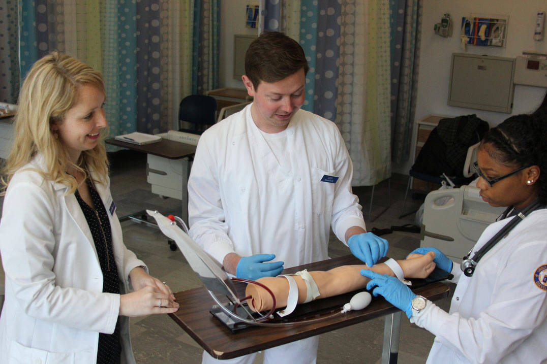 Accelerated nursing students in Ohio practice on phlebotomy arm