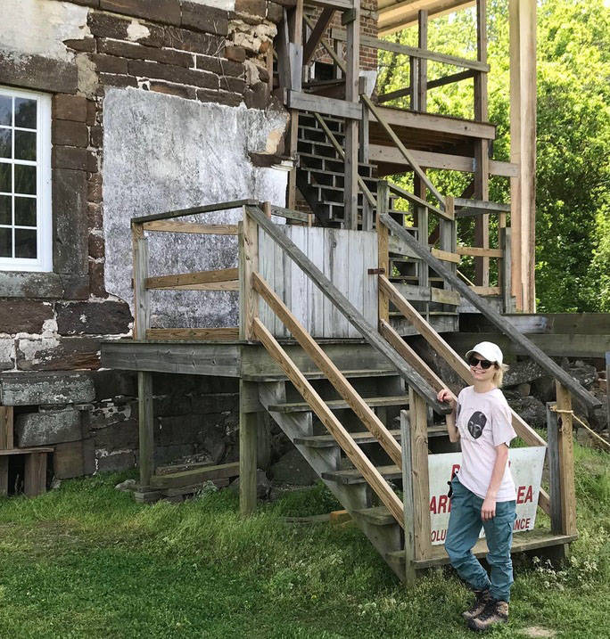 Historic preservation student poses at construction site during internship