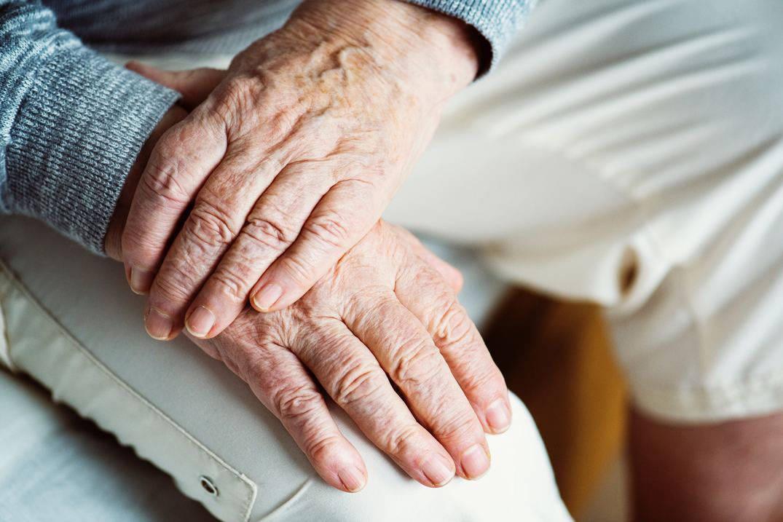 Senior hands folded in lap