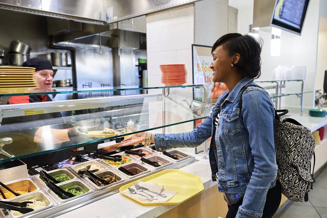 A student selects food from a salad bar in the dining hall at Ursuline College