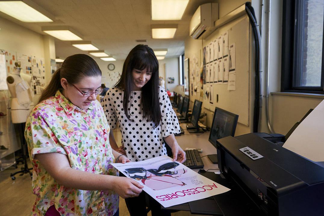 Fashion design student and professor examining InDesign work