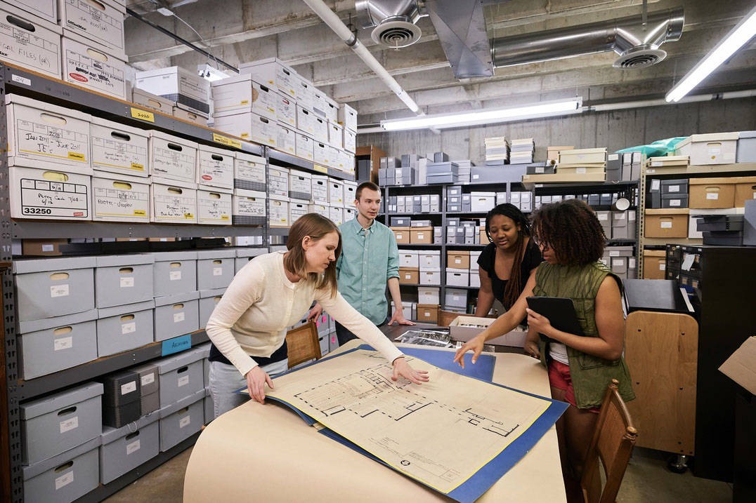 Students and faculty examine historic documents and blueprints at Ursuline College