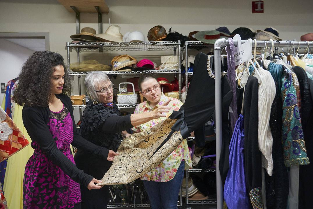 Fashion design students and professor examine historic dress