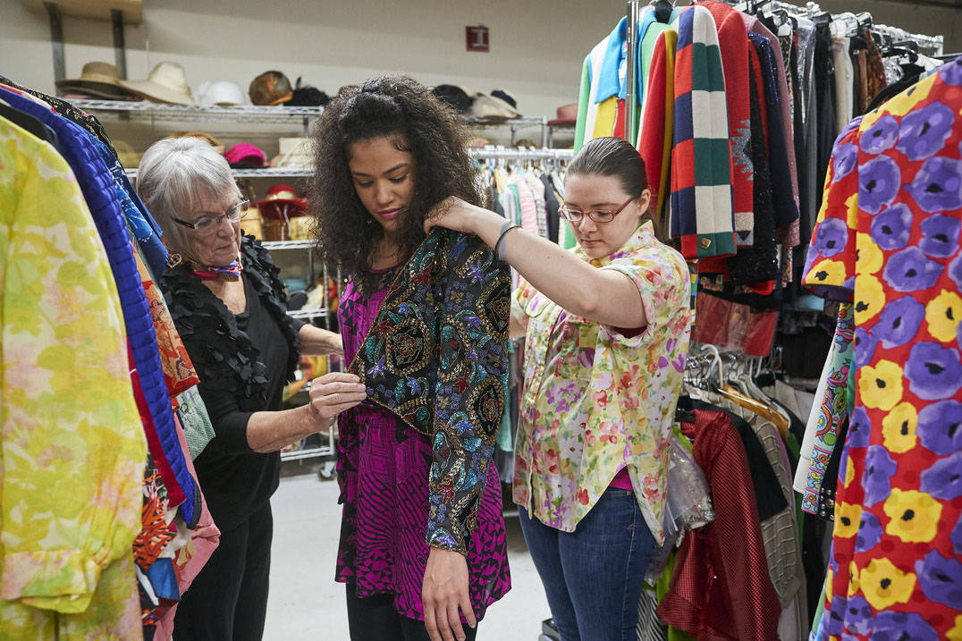 Fashion design student trying on jacket in Historic Costume Study